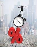 Affärsman som balanserar på ringklockan och rött procentsatstecken Royaltyfri Fotografi