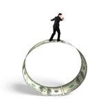 Affärsman som balanserar på rulle av dollarräkningar Arkivfoton
