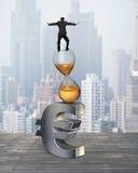 Affärsman som balanserar på timglas- och eurotecken Arkivbild