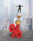 Affärsman som balanserar på timglaset och rött procentsatstecken Arkivbilder