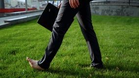 Affärsman som barfota går på grönt gräs nära kontorsmitten, avkoppling royaltyfria foton