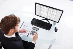 Affärsman som beräknar kostnader på kontorsskrivbordet Royaltyfria Bilder