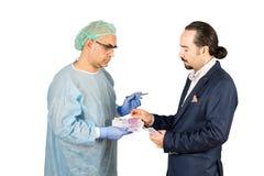 Affärsman som betalar kirurgiavgiften till kirurgen som isoleras på vit bakgrund Royaltyfri Foto