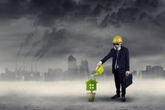 Affärsman som bevattnar växten under luftförorening arkivfoto