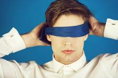 Affärsman som bindas för ögonen på med bandet på blå bakgrund arkivbild