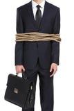 Affärsman som binds med repet arkivbild