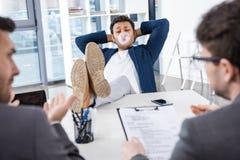 Affärsman som blåser bubbelgum med ben på tabellen under jobbintervju Arkivbild