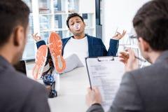 Affärsman som blåser bubbelgum med ben på tabellen under jobbintervju Royaltyfri Foto