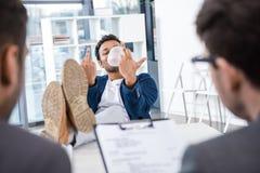 Affärsman som blåser bubbelgum och visar långfingrar under jobbintervju Royaltyfri Bild