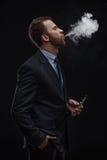 Affärsman som blåser rök av den elektroniska cigaretten Arkivbilder