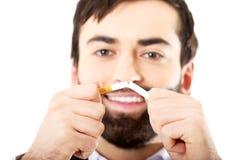 Affärsman som bryter en cigarett Arkivbilder