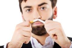 Affärsman som bryter en cigarett arkivfoto