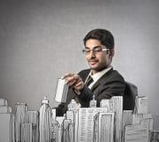 Affärsman som buliding en stad arkivfoto