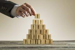 Affärsman som bygger en pyramid av träsnitt med folksilhou Royaltyfri Bild