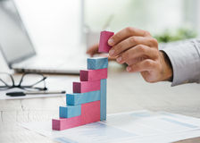 Affärsman som bygger en växande finansiell graf royaltyfria bilder
