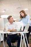 Affärsman som diskuterar med den kvinnliga kollegan, medan sitta på skrivbordet Royaltyfri Fotografi