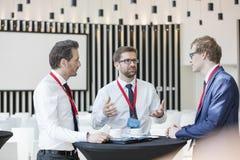 Affärsman som diskuterar med kollegor under kaffeavbrott i konventcentrum Royaltyfria Bilder