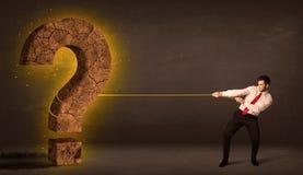 Affärsman som drar en stor fast sten för frågefläck Royaltyfri Fotografi