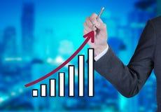 Affärsman som drar en växande graf royaltyfria foton