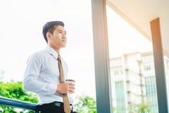 Affärsman som dricker ett kaffe och ser sikt och som tänker succ Arkivbild
