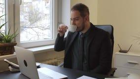 affärsman som dricker kaffe som i regeringsställning som arbetar på bärbara datorn tar anmärkningar stock video