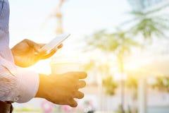 Affärsman som dricker varmt kaffe och använder smartphonen royaltyfri foto