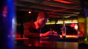 Affärsman som dricker whisky i stången, gnidande huvud i desperat, konkurs arkivfilmer