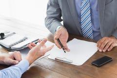 Affärsman som förklarar avtalet till Co-arbetaren Arkivfoton