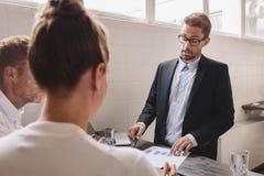 Affärsman som förklarar nya affärsidéer till coworkeren Arkivbilder
