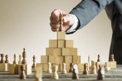 Affärsman som förlägger ett schackstycke på kvarter Royaltyfria Foton