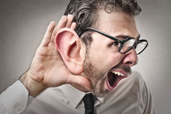 Affärsman som försöker att lyssna till Arkivbilder