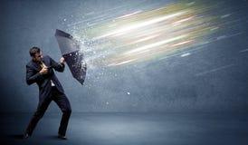 Affärsman som försvarar ljusa strålar med paraplybegrepp Royaltyfri Foto