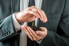 Affärsman som fostrar en spira planta royaltyfria foton