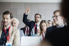 Affärsman som frågar frågor under seminarium Royaltyfri Foto