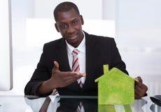 Affärsman som framlägger det ekologiska huset Arkivfoto