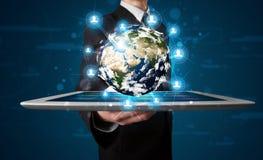 Affärsman som framlägger jordklotet för jord 3d i tablet Fotografering för Bildbyråer