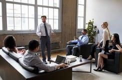 Affärsman som framlägger till kollegor på ett informellt möte royaltyfri foto