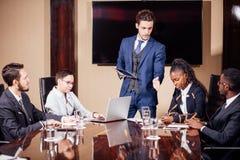 Affärsman som framlägger till kollegor på ett möte arkivbild
