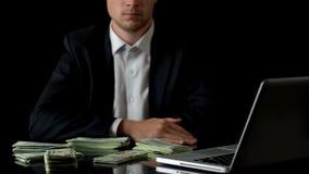 Affärsman som framme sitter av bärbara datorn, pengar på tabellen, olagligt avtal, bestickning arkivbild