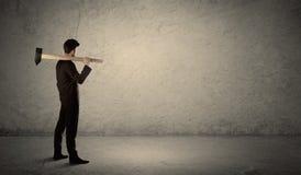 Affärsman som framme står av en grungy vägg med en hammare Arkivfoton