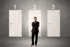 Affärsman som framme tänker av tre dörrar Arkivfoton