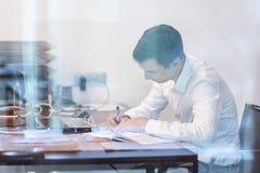 Affärsman som fungerar med förlagor i kontoret Arkivfoton