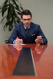 Affärsman som fungerar med förlagor i kontoret Royaltyfria Bilder