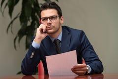 Affärsman som fungerar med förlagor i kontoret Royaltyfria Foton
