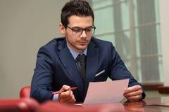 Affärsman som fungerar med förlagor i kontoret Arkivfoto