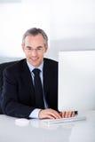 Affärsman som fungerar på datoren Royaltyfria Bilder