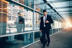 Affärsman som går med bagage och använder mobiltelefonen på airpoen royaltyfria bilder