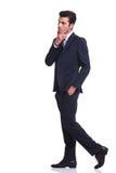 Affärsman som går med en hand i hans fack arkivfoto