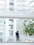 Affärsman som går med mobiltelefonen Arkivfoto