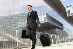 Affärsman som går med spårvagnen och påsen Arkivbild